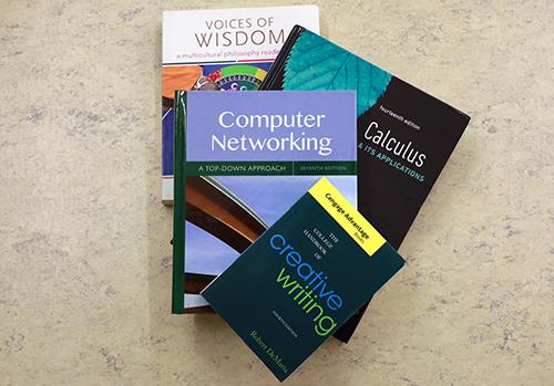 three textbooks sitting on desk
